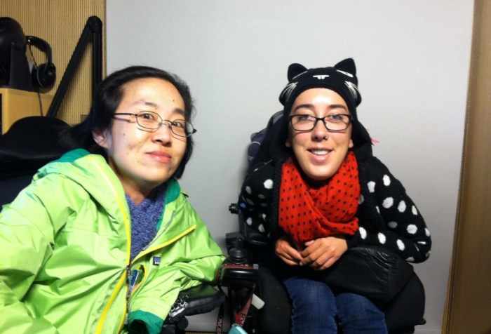 Image of two women with disabilities who use wheelchairs. On the left is an Asian woman with glasses and a green jacket. On the right is a white woman with glasses and a black sweater with white polka dots and a red scarf