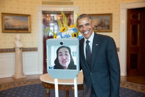 Image of President Barack Obama in the Blue Room of the White House standing next to Alice Wong who is on a screen in a telepresence robot.