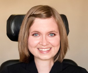Headshot of a young white woman with blue eyes with chin-length golden brown hair. She is in a wheelchair and a headrest is behind her.