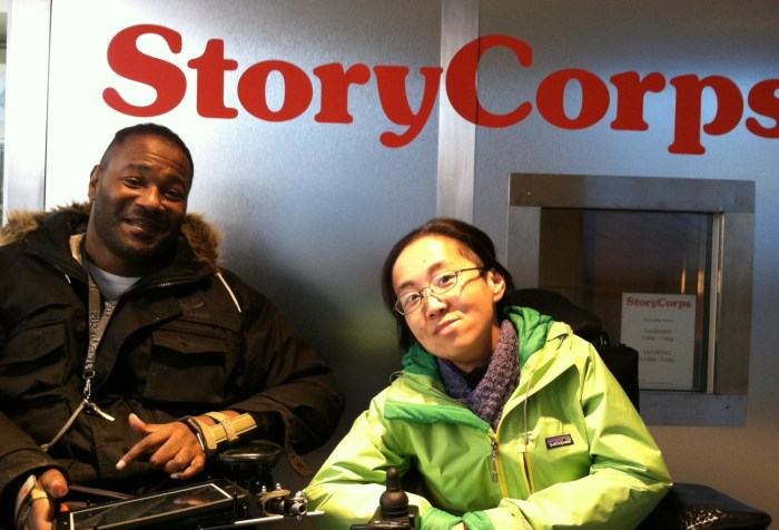 2 individuals in wheelchairs in front of a StoryCorps listening booth. The person on the left is a middle-aged African American man in a black jacket w/ short braids. The person on the right is a middle-aged Asian American woman wearing a green jacket and glasses. Both are smiling at the camera.