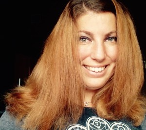 A young white woman against a black background, she has long brown reddish hair. She is smiling at the camera and wearing a gray top with a white lace design on the front