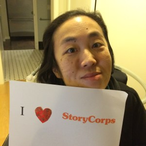 "Image of an Asian American woman in a wheelchair holding a paper sign that reads, ""I [heart symbol] StoryCorps"""