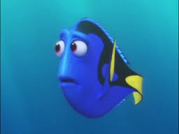 """An animated scene from the Pixar film """"Finding Dory."""" Dory, a regal blue tang fish looks pensive and sad."""