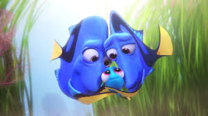 """An animated scene from the Pixar film """"Finding Dory."""" Two parents who are blue tang fish embracing their little baby fish in the center."""