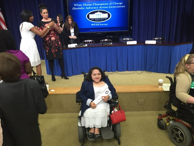 Image of Sandy Ho, a young Asian American woman in a wheelchair in front of a stage at the White House. Behind her is a long table with a blue tablecloth and a large television screen showing the logo of the White House.