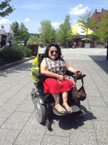 Image of Sandy Ho, a young Asian American woman in a wheelchair, outdoors on a sunny day. She is wearing sunglasses.