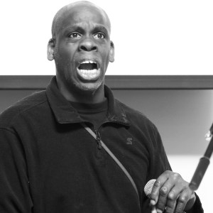 Black and white image of a middle-aged Black disabled man wearing a dark shirt, with a cane nearby his hand.