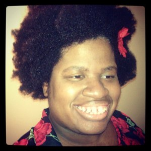 An Instagram image that is square shaped with a black border. Image of a Black woman with curly natural hair with a small red bow on the left side of her hair. She is wearing a black long-sleeved shirt with a print of red flowers. She is smiling at the camera and looking slighting off camera.