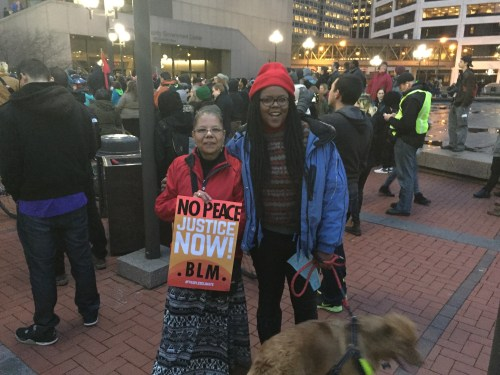 """Two women of color at an outdoor protest. One is holding a sign that says, """"No Peace. Justice Now! BLM"""" The other woman is holding the leash with a dog"""