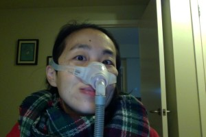 Image of an Asian American woman in her bedroom. She's in a wheelchair and wearing a mask around her nose with a tube. She has a multi-colored plaid scarf around her neck.