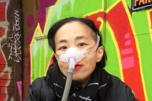Asian American woman in a wheelchair. She is wearing a black jacket with a black patterned scarf. She is wearing a mask over her nose with a tube for her Bi-Pap machine. Behind her is a wall full of colorful graffiti