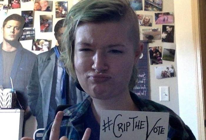"""Image of a young white woman with blonde hair combed to the right side of her face, the left side of her hair is shaved off. Behind her are photos and poster typical of any college dorm room or bedroom. Her eyes are squinting and her lips are pursed as her right hand is making a """"rock on"""" pose with her middle and ring finger downward while the others are standing up. On the left hand she is holding a white index card that reads, #CripTheVote."""