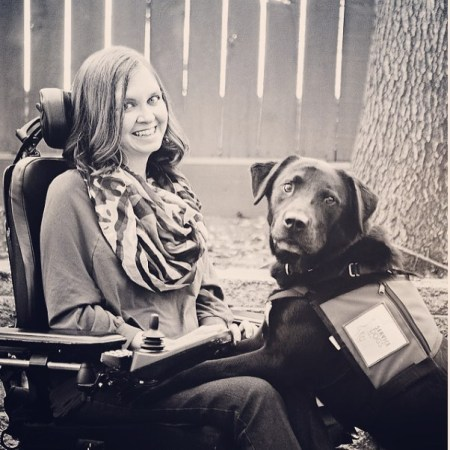 Young white woman in a sepia-tone photo. She is in a power chair and a black labrador retriever that is her service animal has its two front paws on her lap.