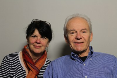 Photo of two people against a blank white background. An older white man is on the right side of the image. He has short white hair and wearing a button-down long-sleeved blue shirt. To the left of him in the image a white woman with dark brown hair. A pair of glasses are positioned on top of her head. She is wearing dangly earrings, a multicolored scarf wrapped around her neck and a black-and-white striped shirt. Both are smiling at the camera.
