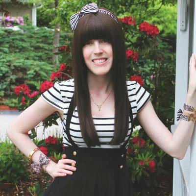 A young white woman with long brown hair and bangs over her eyes. She is wearing a short-sleeved white-and-black striped shirt and black pants with suspenders. Her left arm is leaning against a wall. Behind her is greenery with red flowers.