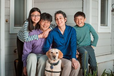 Family portrait outside of a home. A multiracial family. An Asian Man sitting next to a multiracial woman. The left of the man is a young multiracial girl with long hair and glasses. To the right of the woman is a young multiracial boy with short hair. A golden retriever service animal is sitting front and center between the two adults.
