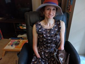 """This is a photograph of an amputee woman, wearing an orange and tan hat and a blue dress with a print of brown, grey and white cat faces on it. She is seated in a chair and holds a brown leather purse on her lap. Her right art ends with a pointed tip, and her left arm, shorter than the right one, ends with a more rounded """"hand"""" with a fleshy ball on it. She looks at the camera with a large smile."""