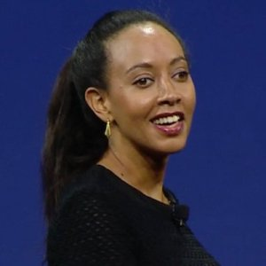 Photo with a blue background with a young Black woman with long hair pulled back. Her body is turned at an angle toward the camera. She is wearing a black sweater, gold earrings. She is smiling.