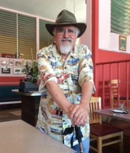 Older white man with a fedora-type hat and a short-sleeve printed shirt. He is standing and both of his hands are resting on top of his cane. He has white hair and a white beard. He is standing inside a cafe.