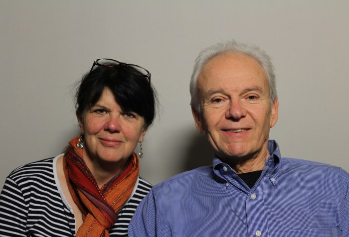 A photo featuring Anthony Tusler and Fran Osborne taken on June 16, 2016: Two people sitting next to each other. The woman on the left is Fran Osborne who appears to be white. She has long dark hair pulled back, with eye glasses on top of her head. She is wearing a black and white striped shirt with an orange scarf tied around her neck. The man on the right is Anthony Tusker who appears to be white. He is wearing a light blue button-down shirt with a black t-shirt inside. He is smiling, and his hair is white and combed back.