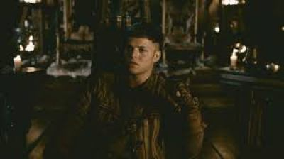 Image description: screenshot from an episode of Vikings, an original series on the History Channel. Ivar the Boneless is a young Viking warrior and he is sitting alone in the Great Hall of Kattegat, the home of Ivar and his family. He looks like he is contemplating something.