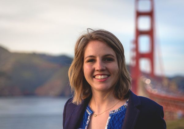 Image description: a young white woman with shoulder-length blonde hair standing outdoors with the Golden Gate Bridge and the Marin Headlands behind her. She is wearing a navy blazer with a blue sweater inside.