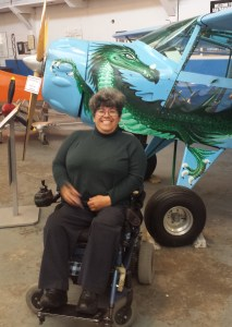 Alicia Contreras, sitting on her power chair next to a small plane at the airplane museum in Oakland, California.