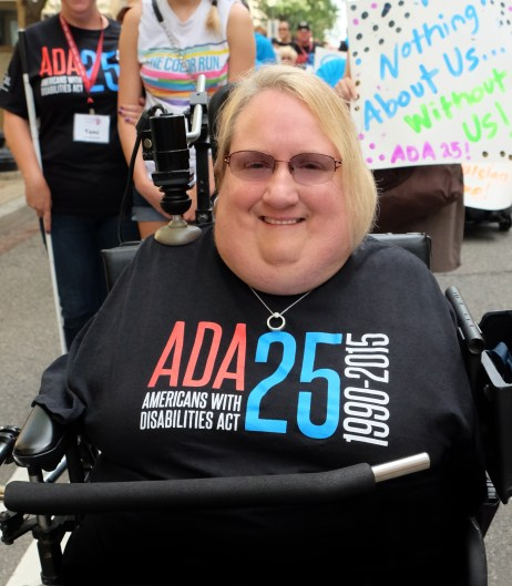 "Marilee Adamski-Smith, a woman with short blond hair, is in a wheelchair with a bar across her torso. She is wearing a black t-shirt that says ""ADA 25 Americans with Disabilities Act 1990-2015."" She does not have any arms or legs and has a joystick resting on her right shoulder for her wheelchair."
