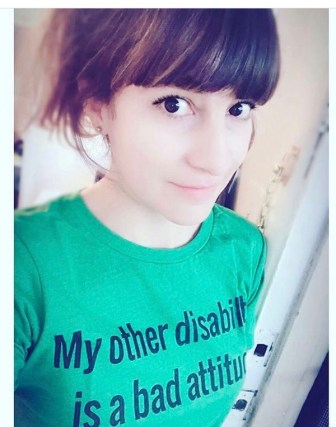 "Pictured is a Mestiza woman with big brown eyes and pale skin color. She is positioned at a side angle with respect to the camera and is wearing a green t-shirt that reads ""My other disability is a bad attitude""."