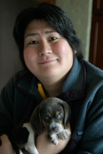 Image description: photo showing Karen Nakamura, an Asian woman holding a small grey beagle puppy — her service dog, Momo, who is now fully grown.