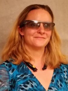 Photo description: A middle aged white woman smiling, as she receives visual interpretation from a remote human guide who gets a bird's eye view via the camera on her AirA sunglasses. There is a Bluetooth receiver on her neck.