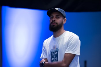 Image Description: Dustin, a Black man, stands in front of a blue backdrop with his arms folded looking out into an audience. He is wearing a dark blue hat and a white t-shirt with the #CripTheVote logo which is a 4 square box depicting different forms of disability.