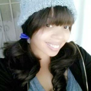 Image description: Woman, wearing a grey knit cap, smiling.