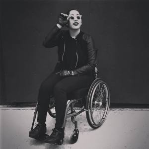 Image Description: black and white photo of Annie, a tall, light brown skinned person with slicked-back hair, dressed in all black and sunglasses, seated in a manual wheelchair.