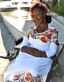 Image description: Andraéa sitting in her power wheelchair wearing a long, white dress with brightly colored flowers lining the collar and bottom of the dress. She is sitting in front of a wooden ramp with water and the sun shining brightly behind her.