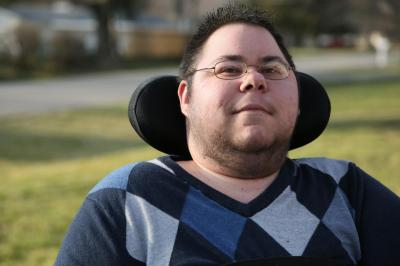 Dominick, a nonbinary trans masculine person looks at the camera, with a slight smile on his face. His eyes are also smiling. He has short, dark spiky hair, and wears glasses. He has stubble along his jaw, cheeks, and chin. He is wearing a argyle sweater with various shades of blue, gray, and black. His wheelchair headrest is visible behind his head, and there is green grass and the neighborhood behind him, faded in the background.