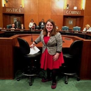 Image description: Maria Town, a young white woman with long brown hair standing behind a room that looks like a hearing room in the city hall of Houston, TX. She is wearing a bright red dress with a black and white blazer.