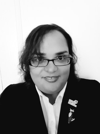 Black and white frontal headshot picture of a Latina woman in her mid to late 20s. She is smiling, has eyeglasses and is wearing a white shirt with a black blazer. In her lapel she is wearing a pin with the logo of the National LGBTQ Task Force, and a brooch in the shape of an owl.