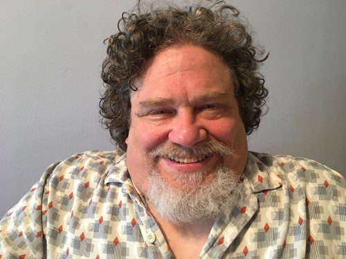 A middle-aged man smiles, He has brown curly hair, a grey goatee and wears a vintage looking cocktail hour shirt.