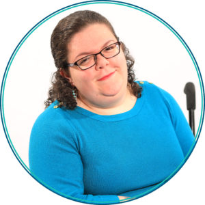 Image of Emily Ladau a young white woman with curly brown hair. She is wearing glasses and a blue sweater. She is sitting in a wheelchair.