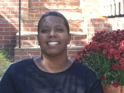 Image description: Woman smiling and sitting on brick stairs in black shirt with flowers behind her. This is Dara Baldwin - African American woman, social justice activist and disability rights advocate.