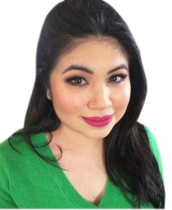 A picture of a woman sitting. Image is cut off at the chest. She is looking straight at the camera, and smiling with bright pink lipstick and pink blush on her cheeks. Long black hair is asymmetrical and falls to the right side of her face. She has long lashes and brown eyes. Wearing a soft, green sweater. Background of picture is white--no furniture.