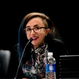 A young white woman wearing eyeglasses with long hair with blue streaks. She is looking sideways and smiling with a microphone in front of her. She is wearing a multicolored print shirt with a black jacket. The background is black.