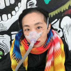 Photo of Alice Wong, Founder and Director of the Disability Visibility Project®, an Asian American woman wearing a multicolored scarf and bright red lipstick. She has a Bi-Pap mask over her nose attached with a gray tube. She is wearing a black jacket and standing behind colorful street art.