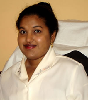 Young Indian American woman with black hair tied in a bun. She is wearing a cream colored shirt and gold earrings.
