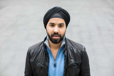 Sikh man wearing a black turban, a black leather jacket and a light blue shirt underneath. He has a beard with black hair and standing outdoors with a gray background. Photo credit: Les Talusan