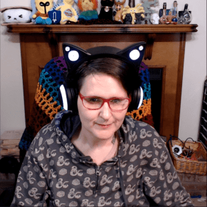 Young white woman wearing pink-framed eyeglasses and a hoodie. She is also wearing headphones that look like black cat ears. Behind her is a wooden mantle full of cute nerdy stuffed creatures.