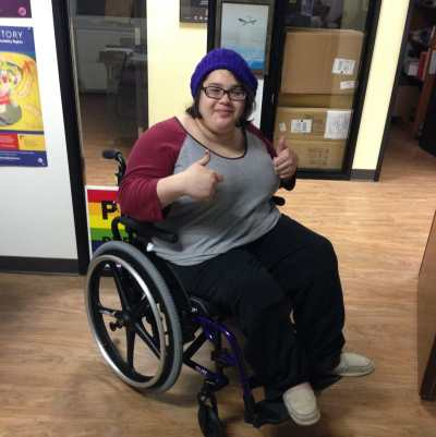 Yolanda Vargas, a young Latinx person in a manual wheelchair wearing a purple knit cap and glasses. She is smiling at the camera with both hands in a thumbs-up position.