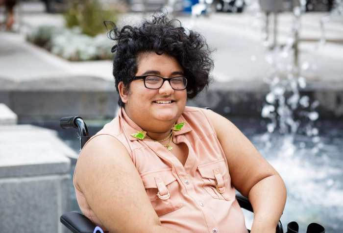 Noor sits in a wheelchair in front of a fountain. He has a curly black undercut and medium golden tan skin. He wears thick glasses, and a sleeveless pink shirt with a set of budgie collar pins. Photo credit: Les Talusan photography