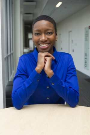 Image of a young genderfluid black person of African descent (TL) wearing a bright blue collared shirt while seated at a desk in a hallway with their hands folded under their chin and elbows leaning against the tabletop. There are windows & doors in the background.